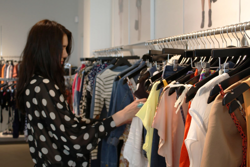 woman-sorting-through-racks-of-clothes